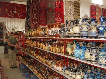 Предметы керамической посуды, сделанные вручную, ковры ручной работы и другие сувениры в магазинчике деревни Психро