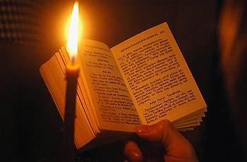 Древняя Библия - монах читает молитвы перед зажженной свечой