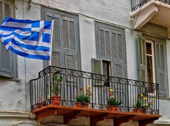 Флаг страны на балконе частного дома в Афинах, Греция