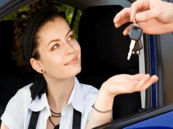 Красивая туристка, получающая ключи от арендованной машины